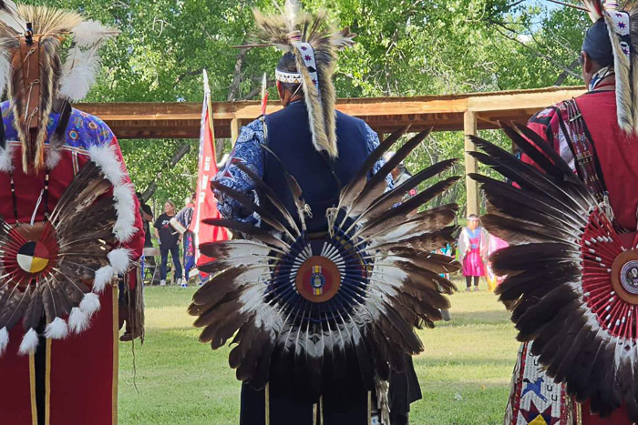 Three traditional dancers rise to participate in a dance ceremony dressed in traditional regalia. The photo was take at the annual Wakpa Waste Wachipi (Good River Pow Wow) at Red Shirt Table, Pine Ridge Reservation, South Dakota.